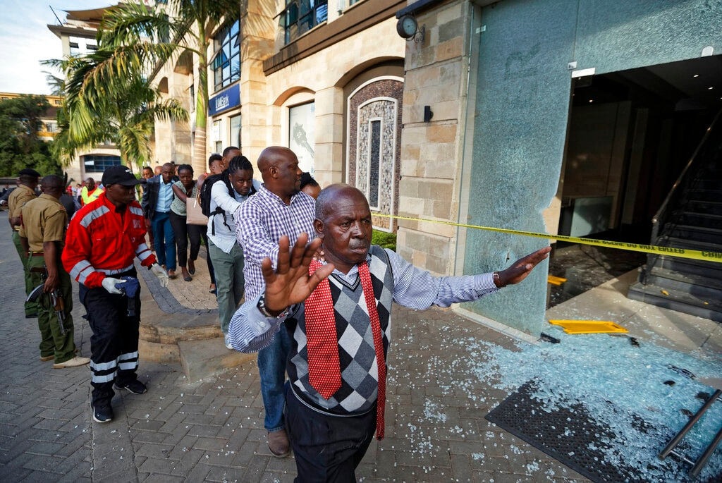 A civilian holds his hands in the air as he and others flee at a hotel complex in Nairobi, Kenya Tuesday, Jan. 15, 2019. Terrorists attacked an upscale hotel complex in Kenya's capital Tuesday, sending people fleeing in panic as explosions and heavy gunfire reverberated through the neighborhood.