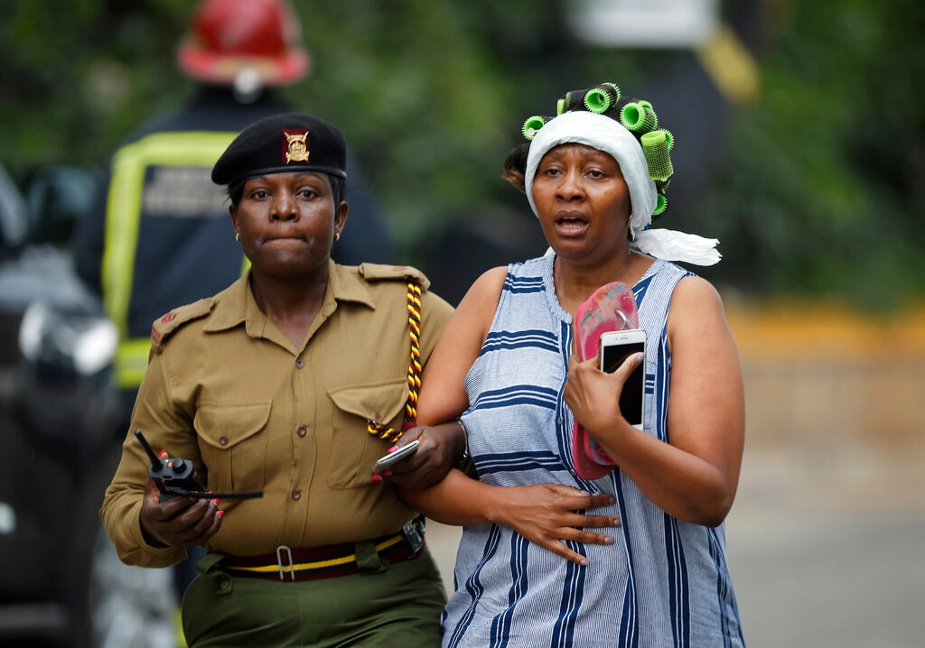 A civilian flees the scene assisted by a member of security forces, at a hotel complex in Nairobi, Kenya Tuesday, Jan. 15, 2019. Terrorists attacked an upscale hotel complex in Kenya's capital Tuesday, sending people fleeing in panic as explosions and heavy gunfire reverberated through the neighborhood.