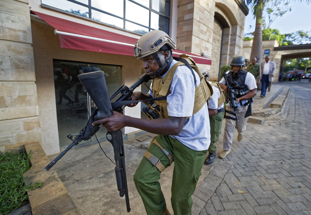 An armed member of Kenyan security forces runs through a hotel complex in Nairobi, Kenya Tuesday, Jan. 15, 2019. Terrorists attacked an upscale hotel complex in Kenya's capital Tuesday, sending people fleeing in panic as explosions and heavy gunfire reverberated through the neighborhood.