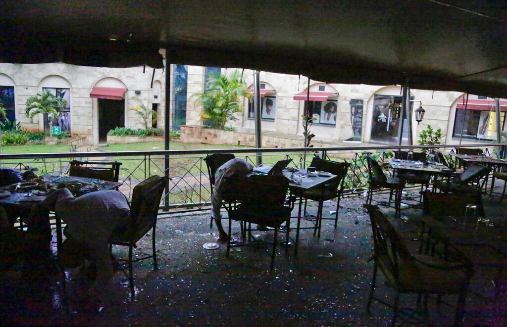 Bodies are seen in a restaurant at the site of an attack on a hotel complex in Nairobi, Kenya, Tuesday, Jan. 15, 2019. Extremists have launched an attack on a luxury hotel in Kenya's capital, sending people fleeing in panic as explosions and heavy gunfire reverberate through the neighborhood. A police officer says he saw bodies,
