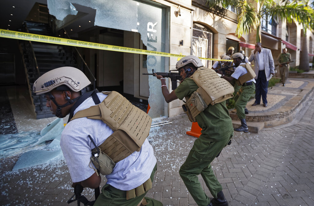 Security forces point their weapons through a shattered door behind which an unexploded grenade lies, at a hotel complex in Nairobi, Kenya, Tuesday, Jan. 15, 2019. Terrorists attacked an upscale hotel complex in Kenya's capital Tuesday, sending people fleeing in panic as explosions and heavy gunfire reverberated through the neighborhood.