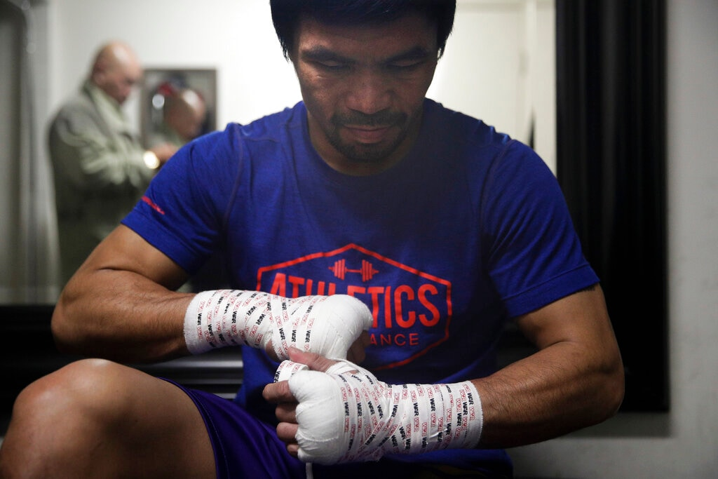 Boxer Manny Pacquiao tapes his hands for a workout at the Wild Card Boxing Club Monday, Jan. 14, 2019, in Los Angeles. The Filipino legend is in the winter of his career, gearing up for what could be one big last fight. Saturday's bout versus Broner isn't it, but Pacquiao trains with the knowledge that a second megafight against Floyd Mayweather could possibly be just months away if all goes well.