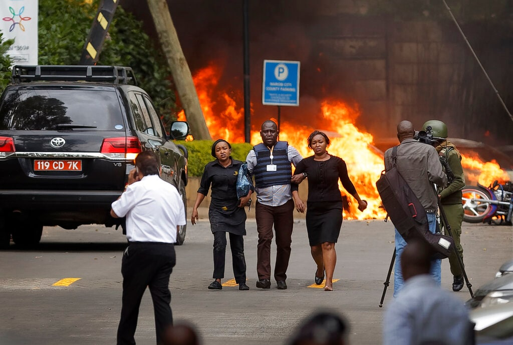 Security forces help civilians flee the scene as cars burn behind, at a hotel complex in Nairobi, Kenya Tuesday, Jan. 15, 2019. Extremists have launched an attack on a luxury hotel in Kenya's capital, sending people fleeing in panic as explosions and heavy gunfire reverberate through the neighborhood. A police officer says he saw bodies,