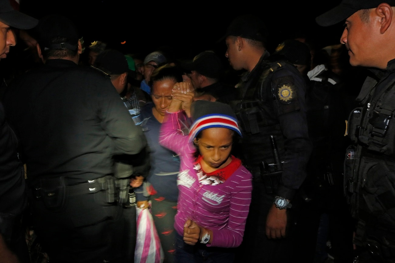 A Honduran migrant family walks between police officers as they enter Guatemala. (AP Photo/Moises Castillo)