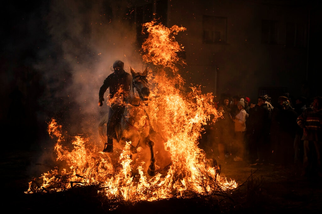 A man rides a horse through a bonfire as part of a ritual in honor of Saint Anthony the Abbot, the patron saint of domestic animals, in San Bartolome de Pinares, Spain, Wednesday, Jan. 16, 2019. On the eve of Saint Anthony's Day, dozens ride their horses through the narrow cobblestone streets of the small village of San Bartolome during the