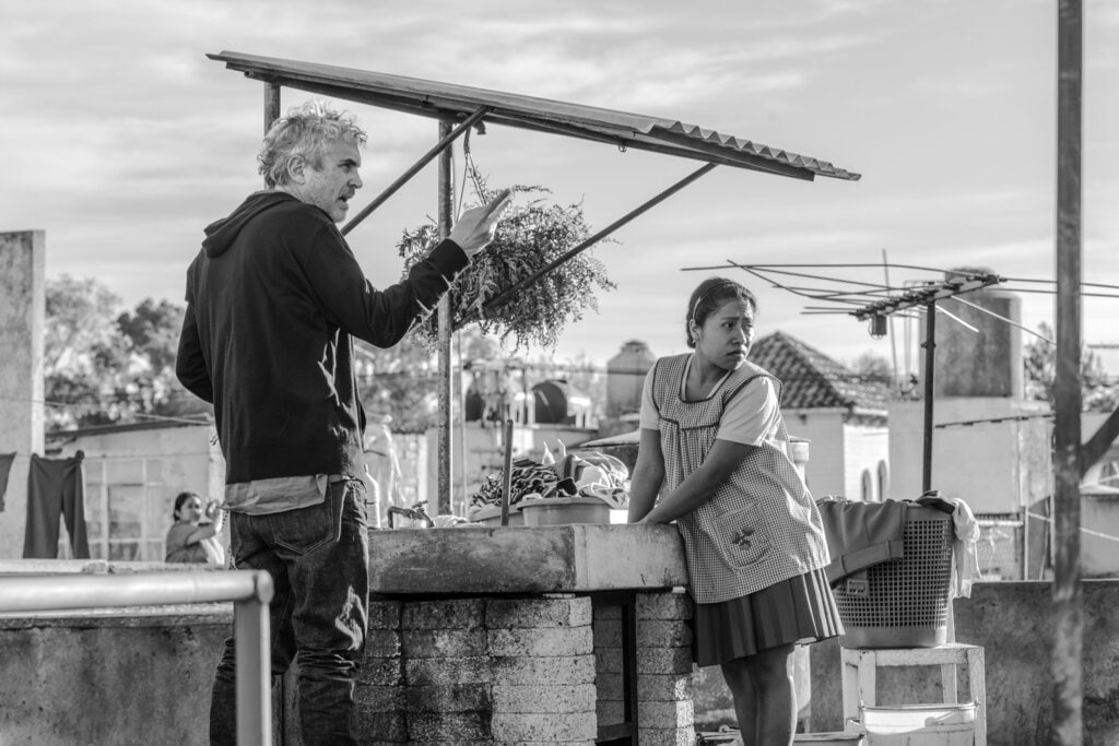 This image released by Netflix shows filmmaker Alfonso Cuaron, left, and Yalitza Aparicio on the set of