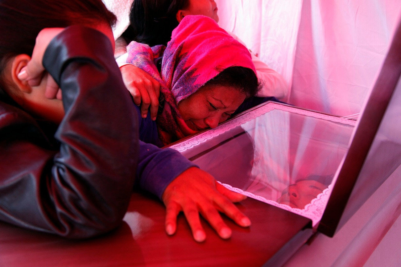 Santos Isabel Escobar weeps beside the coffin of her son, Eddy Fernando Cabrera, 18, during his wake in the same street where he was executed the night before along with four other young people in the Villanueva neighborhood of Tegucigalpa, Honduras. A bleak combination of powerful drivers like poverty and gang violence leads many Hondurans to see emigration as the only possibility for a decent life.(AP Photo/Fernando Antonio)