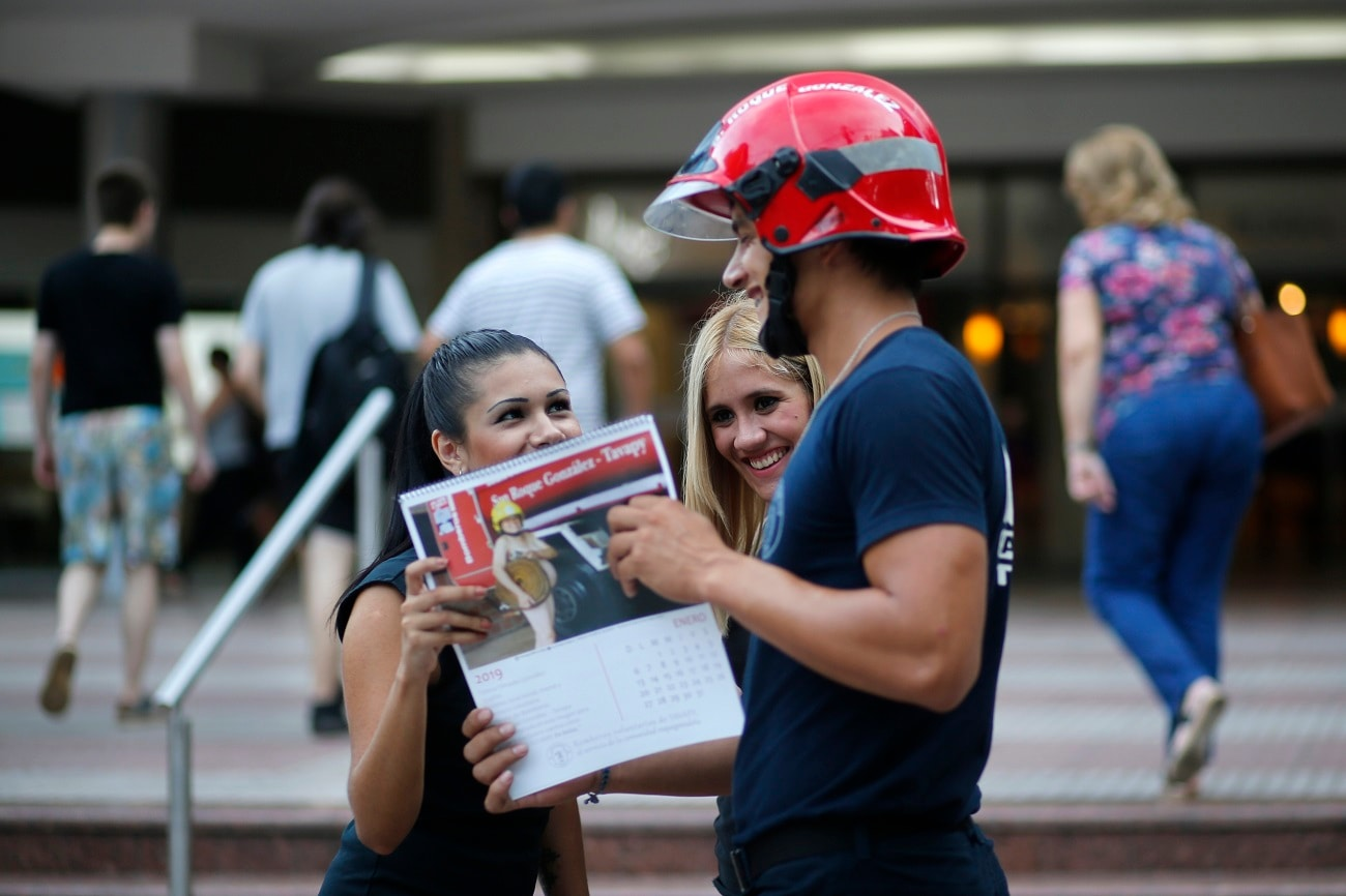 Firefighter Daniel Rodriguez sells calendars to a couple of women in Asuncion, Paraguay. Firefighters in the town of San Roque Gonzalez launched a campaign to sell calendars featuring nude pictures of themselves, to help fund their fire station. (AP Photo/Jorge Saenz)