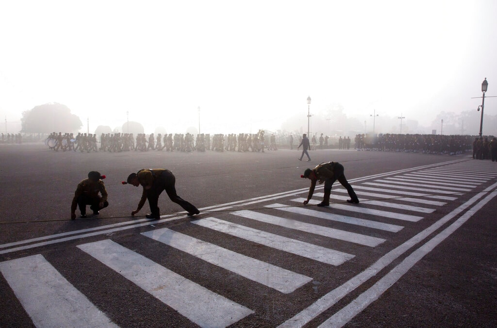 Indian army soldiers put marking on the road for upcoming Republic Day parade amidst early morning smog in New Delhi on January 18. (AP Photo/Manish Swarup)