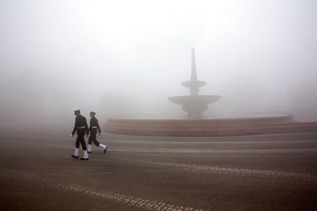 Two Indian Naval officers walk amidst early morning smog in New Delhi on January 18. (AP Photo/Manish Swarup)