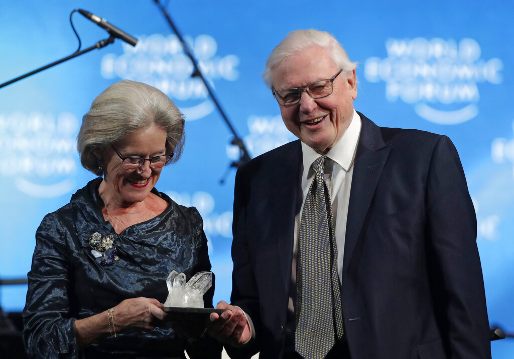 Sir David Attenborough, broadcaster and natural historian, right, smiles as he receives a Crystal Award from Hilde Schwab, Chairwoman and Co-Founder of the World Economic Forum's World Arts Forum, during the ceremony for the Crystal Awards at the annual meeting of the World Economic Forum in Davos, Switzerland, Monday, Jan. 21, 2019. (AP Photo/Markus Schreiber)