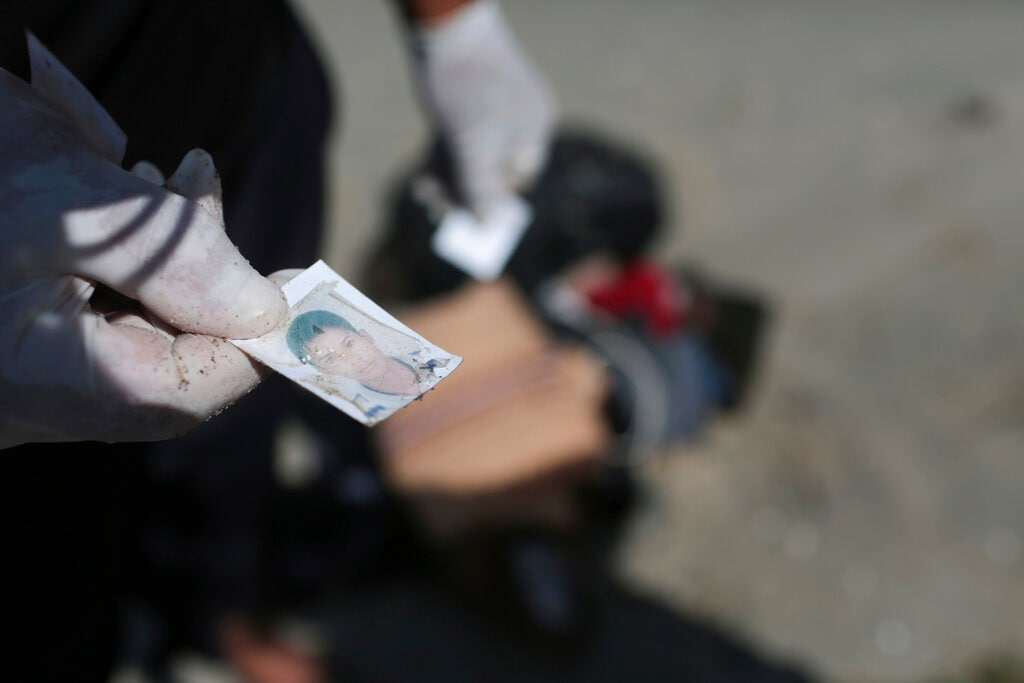 In this Saturday, September 12, 2015 photo, a Libyan Red Crescent worker holds a picture that was found in a bag of belongings that washed up on a beach near the Tunisian Libyan border, not far from Zuwarah, 102 km (63 mi) west of Tripoli, Libya. (AP Photo/Mohamed Ben Khalifa, File)
