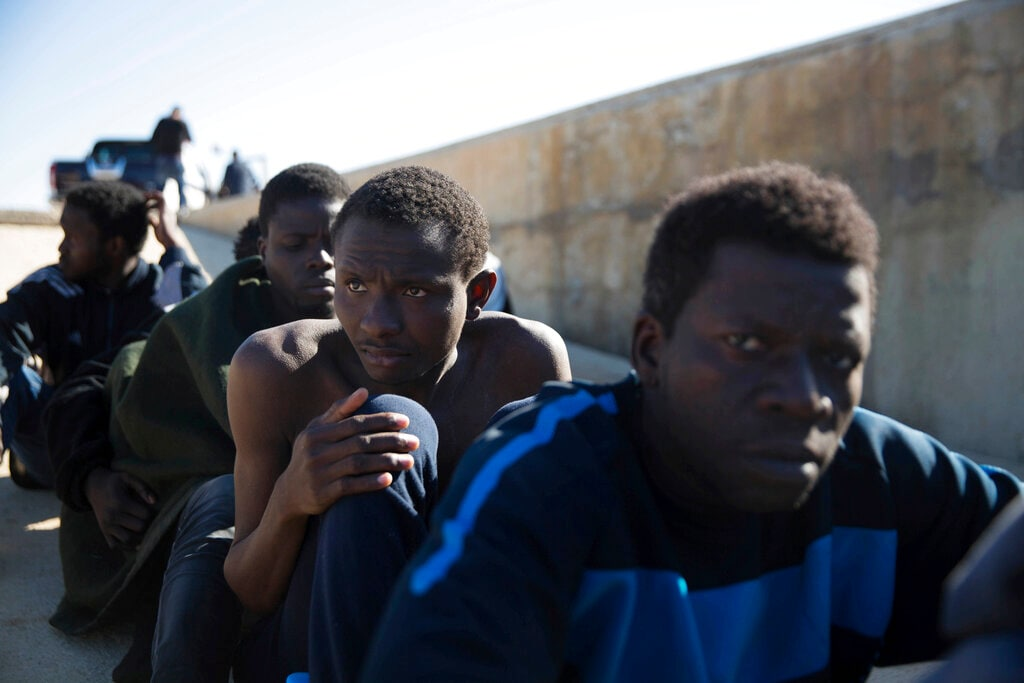 In this March 3, 2017 photo, migrants rest on the sidewalk port of Tripoli they were rescued by the Coast Guard off the coast of Tripoli, Libya. (AP Photo/Mohamed Ben Khalifa, File)