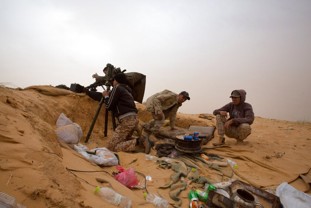 In this Saturday, February 21, 2015 file photo, Libyan soldiers aim their weapons during clashes with militants on the frontline in Al Ajaylat, 120 kilometers (75 miles) west of Tripoli, Libya. (AP Photo/Mohamed Ben Khalifa, File)