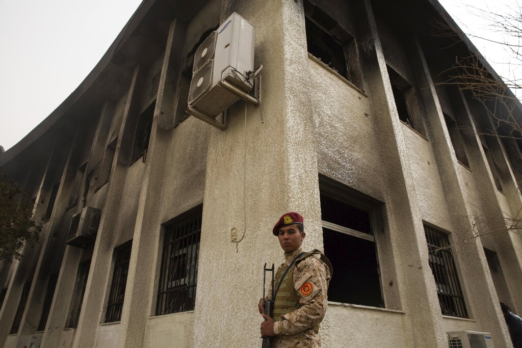 FILE - In this May 2, 2018 photo, a soldier stands outside Libya's high national election commission after a suicide bomb in Tripoli. (AP Photo/Mohamed Ben Khalifa, File)