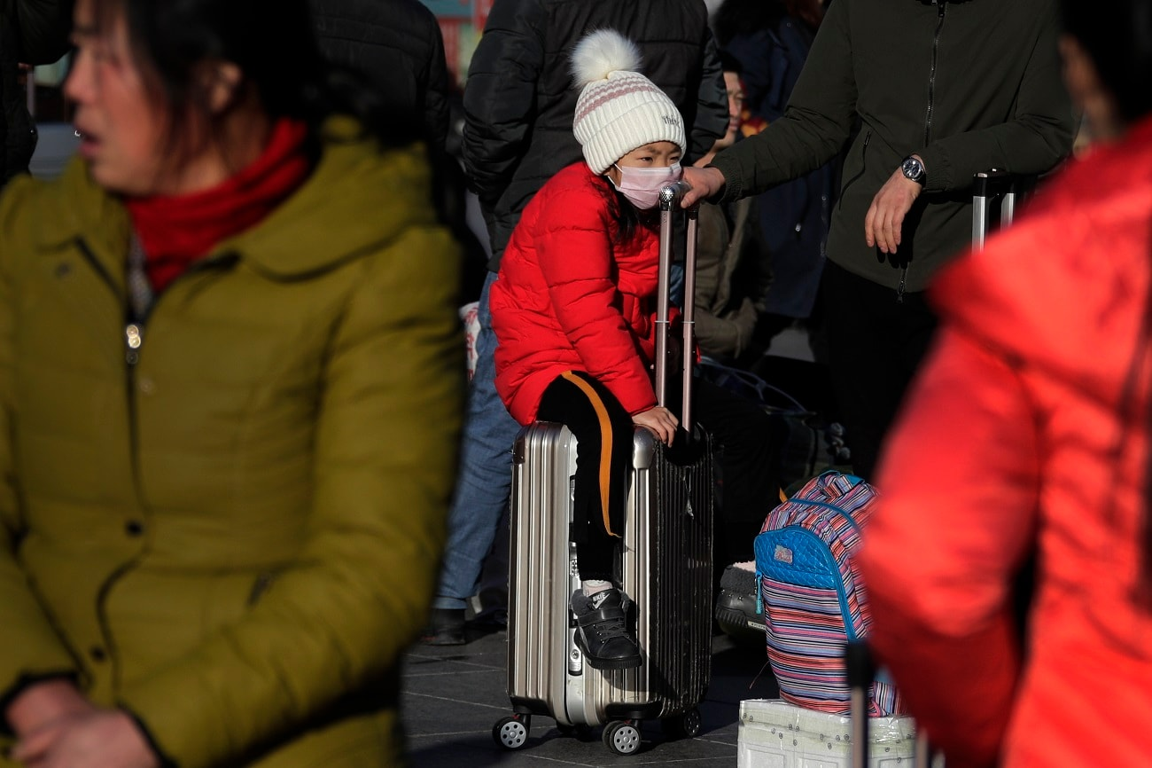 A child sits on a piece of luggage as she and others wait for their train at the Beijing railway station in Beijing. The world's largest annual migration began this week in China with millions of Chinese are traveling to their hometowns to celebrate the Lunar New Year. (AP Photo/Andy Wong, File)