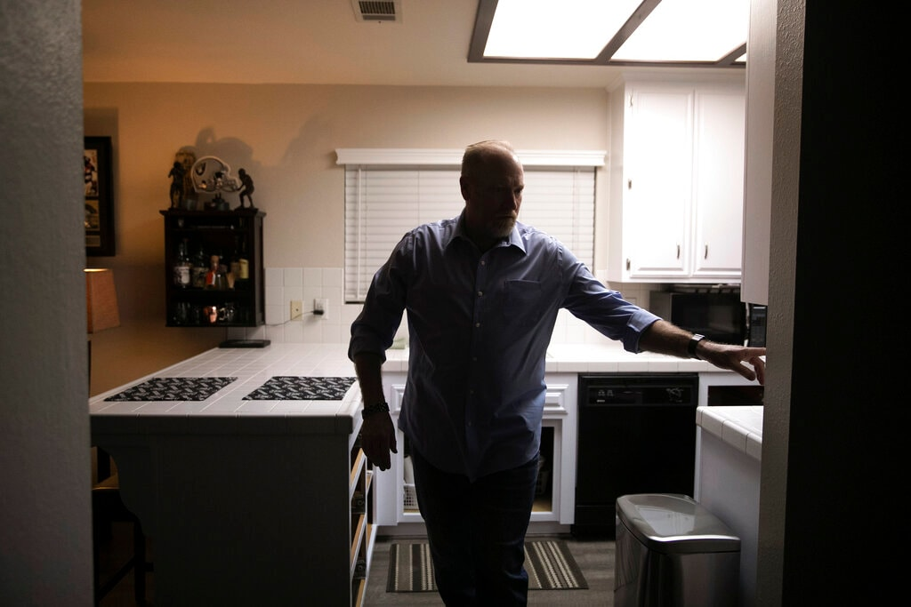 Chris George, a federal employee furloughed from his job as a forestry technician supervisor for the US Department of Agriculture Forest Service, turns the kitchen lights off as he leaves home for a free meal offered to federal workers affected by the government shutdown Saturday, January 19, 2019, in Hemet, California. (AP Photo/Jae C. Hong)