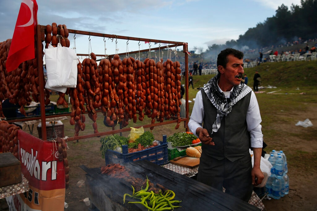 A vendor offers sausages for sale to spectators. (AP Photo/Lefteris Pitarakis)