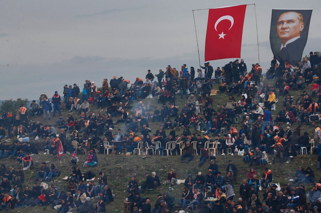 A Turkish flag and a poster of modern Turkey's founder Mustafa Kemal Ataturk are seen on a hill full of spectators overlooking the arena. (AP Photo/Lefteris Pitarakis)