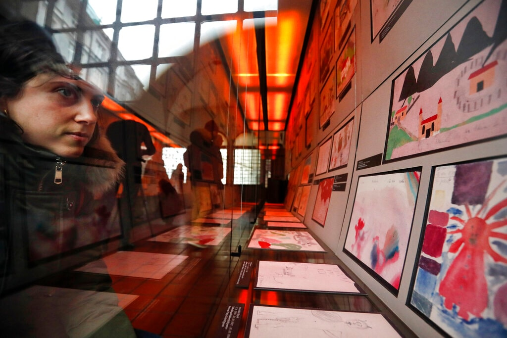 A visitor looks at the collection of drawings at the Jewish Museum in Prague, Czech Republic, Thursday, January 24, 2019, made by Jewish children who passed through the Terezin Ghetto during WWII. (AP Photo/Petr David Josek)