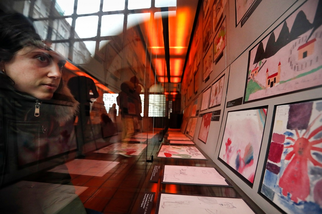 A visitor looks at the collection of drawings at the Jewish Museum in Prague, Czech Republic, made by Jewish children who passed through the Terezin Ghetto during WWII. (AP Photo/Petr David Josek)