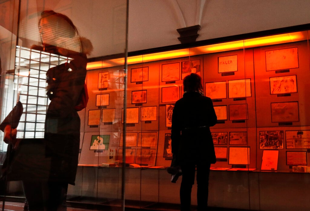 Visitors look at the collection of drawings at the Jewish Museum in Prague, Czech Republic, Thursday, January 24, 2019, made by Jewish children who passed through the Terezin Ghetto during WWII. (AP Photo/Petr David Josek)