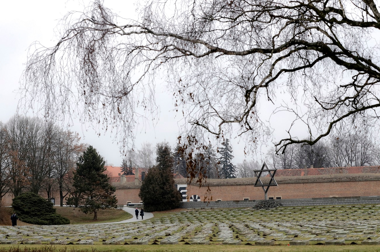 Visitors walk through the cemetery of the former Nazi concentration camp in Terezin, Czech Republic. (AP Photo/Petr David Josek)