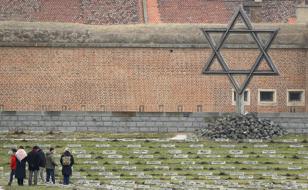 Visitors walk through the cemetery of the former Nazi concentration camp in Terezin, Czech Republic, Thursday, January 24, 2019. (AP Photo/Petr David Josek)