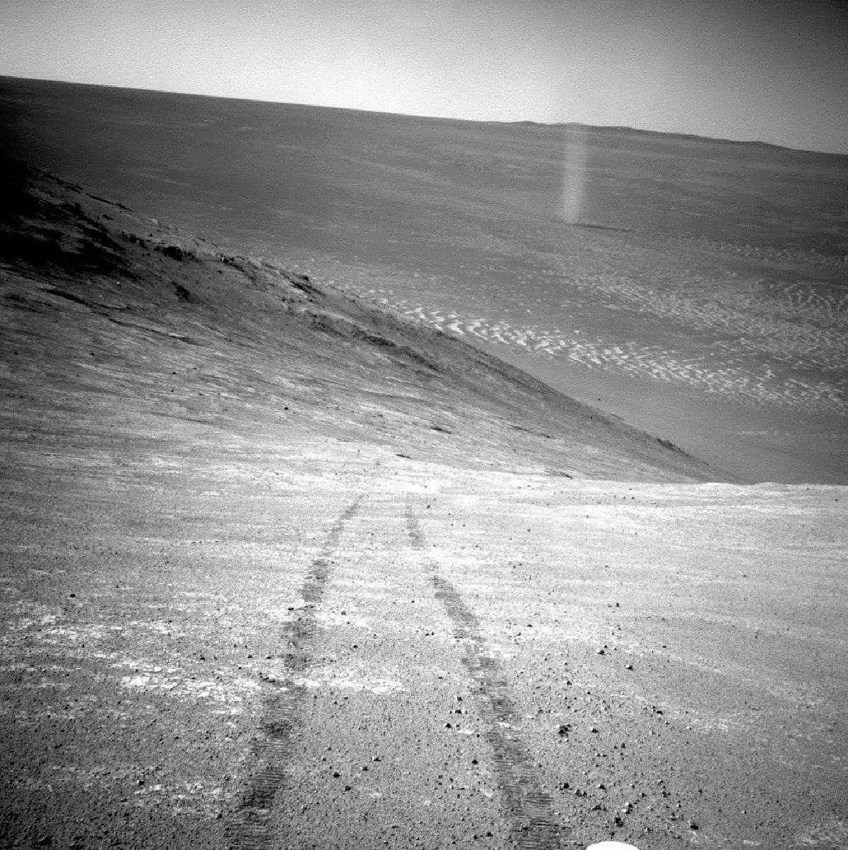 This photo made available by NASA shows a dust devil in a valley on Mars, seen by the Opportunity rover perched on a ridge. The view looks back at the rover's tracks leading up the north-facing slope of