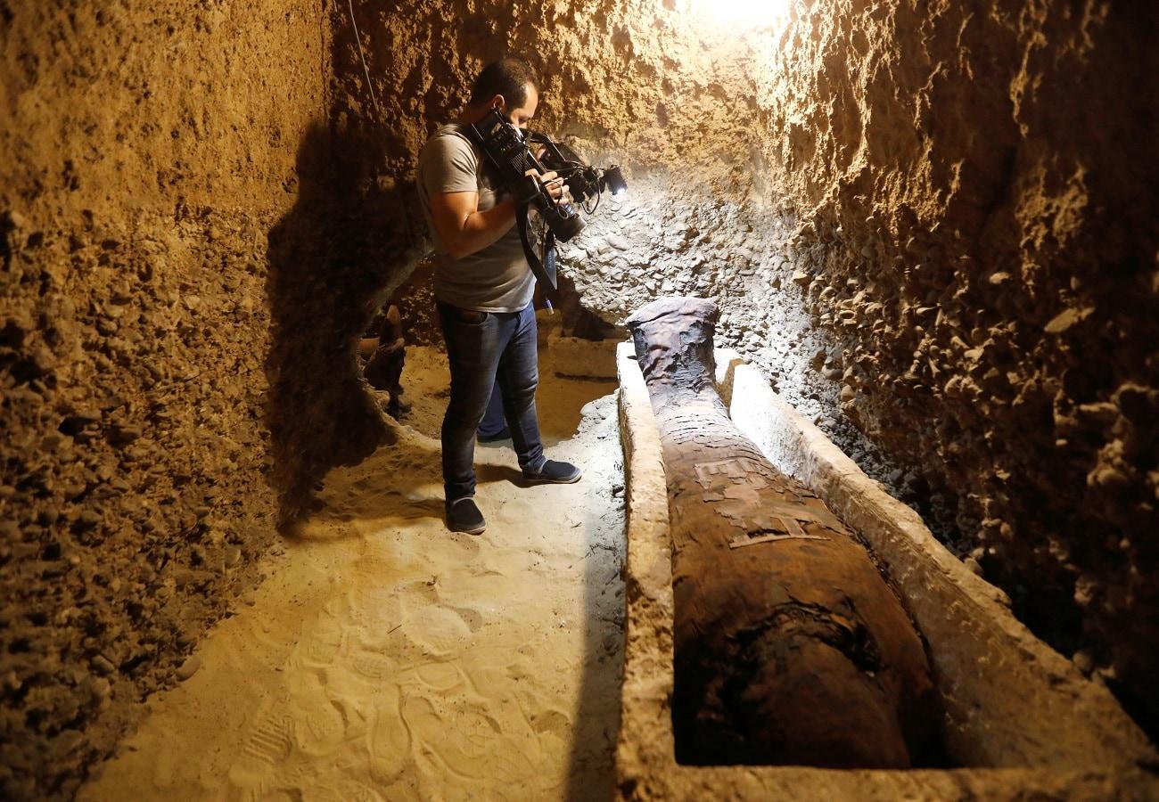 A cameraman films inside a tomb. (REUTERS/Amr Abdallah Dalsh)