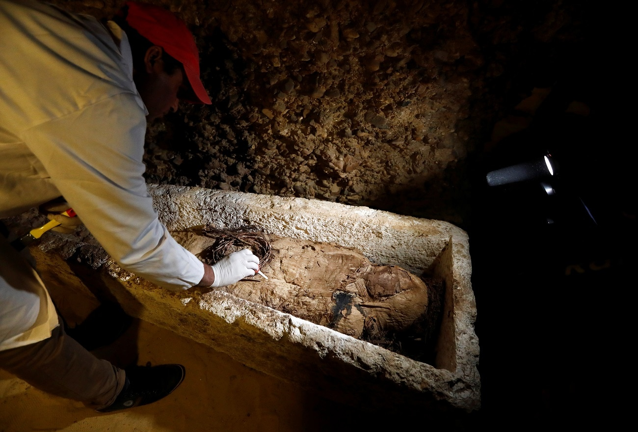 A Egyptian archaeologist examines a mummy in a coffin inside a tomb. (REUTERS/Amr Abdallah Dalsh)