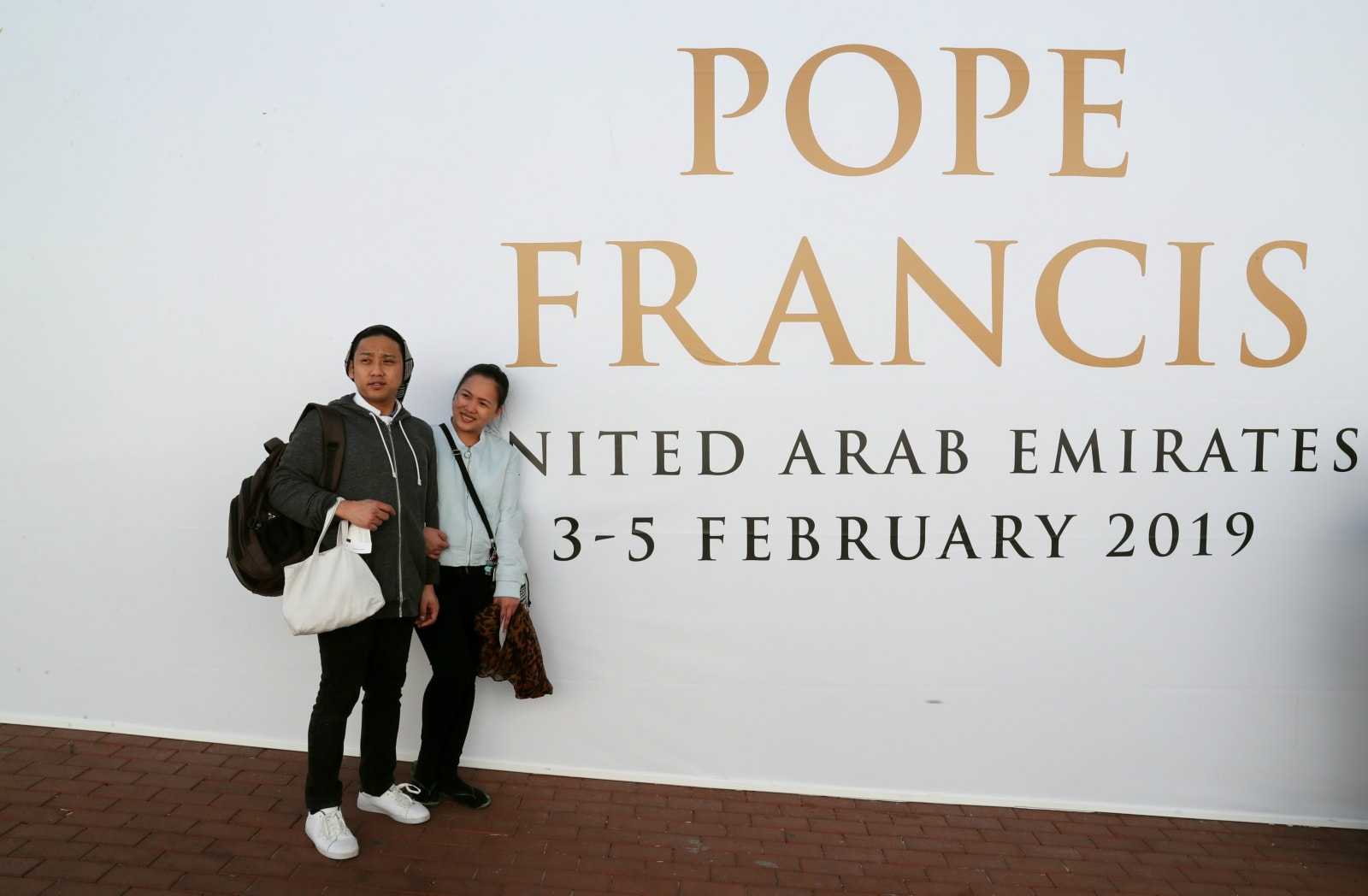 People pose for a photo in front of a sign welcoming Pope Francis in Abu Dhabi, United Arab Emirates, February 5, 2019. REUTERS/Tony Gentile