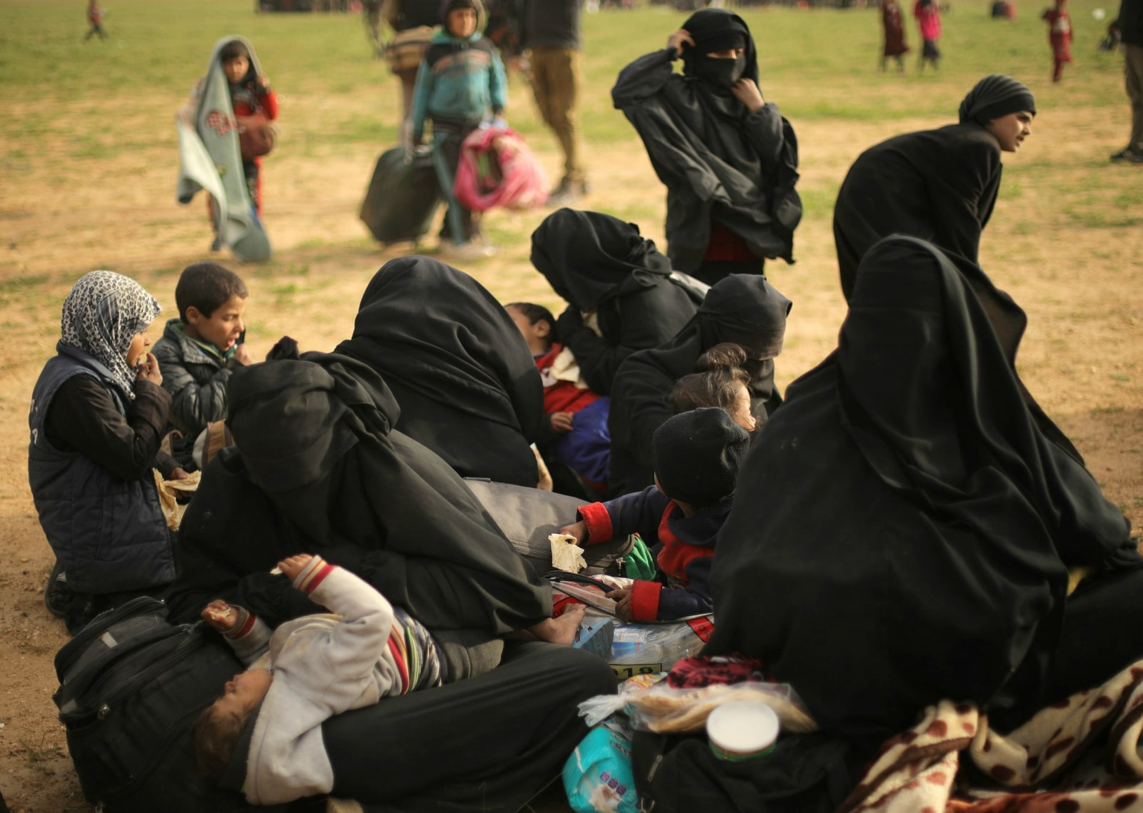 Women sit with their children near the village of Baghouz, Deir Al Zor province, Syria February 26, 2019. REUTERS/Rodi Said