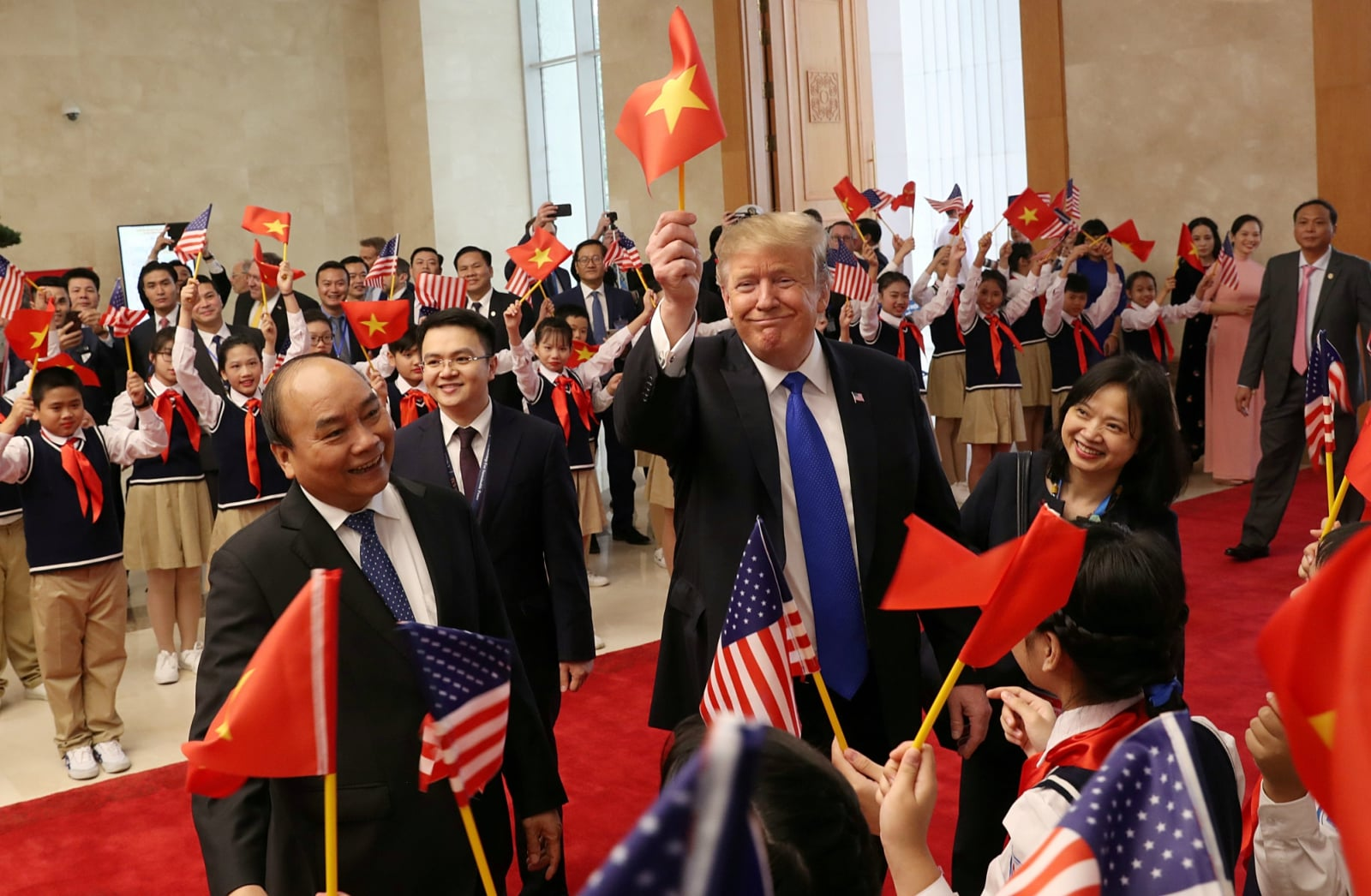 US President Donald Trump waves a Vietnamese flag as he is greeted by students during a meeting with Vietnamese Prime Minister Nguyen Xuan Phuc at the Office of Government Hall in Hanoi, Vietnam, February 27, 2019. REUTERS/Leah Millis