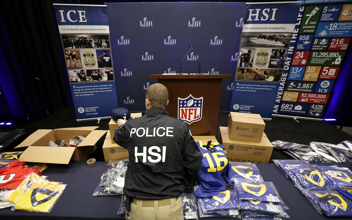 Homeland Security Investigations spokesman Bryan Cox unpacks some of the counterfeit items seized for the NFL Super Bowl 53 football game. (AP Photo/David J. Phillip)