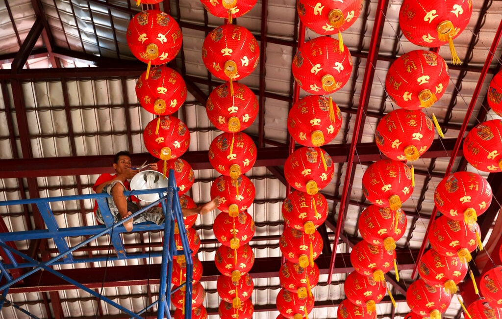 In this January 29, 2019, photo, a worker sits high up in the eves to arrange lanterns in preparation of the Lunar New Year at a temple in Jakarta, Indonesia. (AP Photo/Tatan Syuflana)