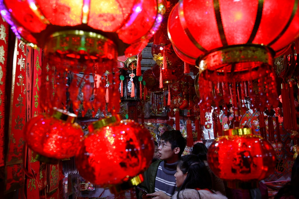 In this Tuesday, January 29, 2019, photo, people shop for Lunar New Year decorations at a market in Beijing. (AP Photo/Andy Wong)