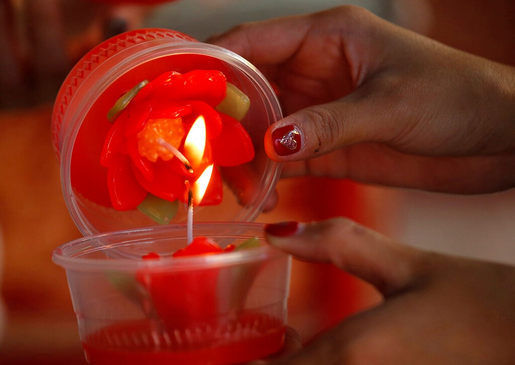 In this Wednesday, January 30, 2019, photo, ethnic Chinese-Thai light candles after praying at the Leng Nuei Yee Chinese temple for the upcoming Lunar New Year in Bangkok, Thailand. (AP Photo/Sakchai Lalit)
