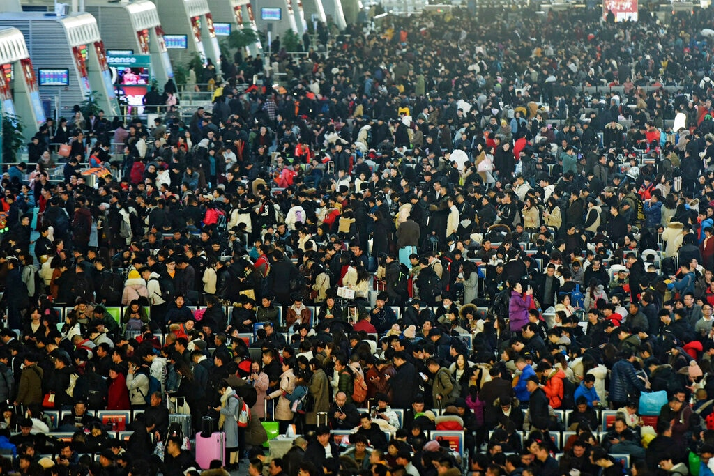 In this January 28, 2019, photo, travelers wait for their trains at a railway station in Hangzhou in east China's Zhejiang province. The world's largest annual migration has begun in China with millions of Chinese are traveling to their hometowns to celebrate the Lunar New Year on February 5 this year which marks the Year of the Pig on the Chinese zodiac. (Chinatopix via AP)