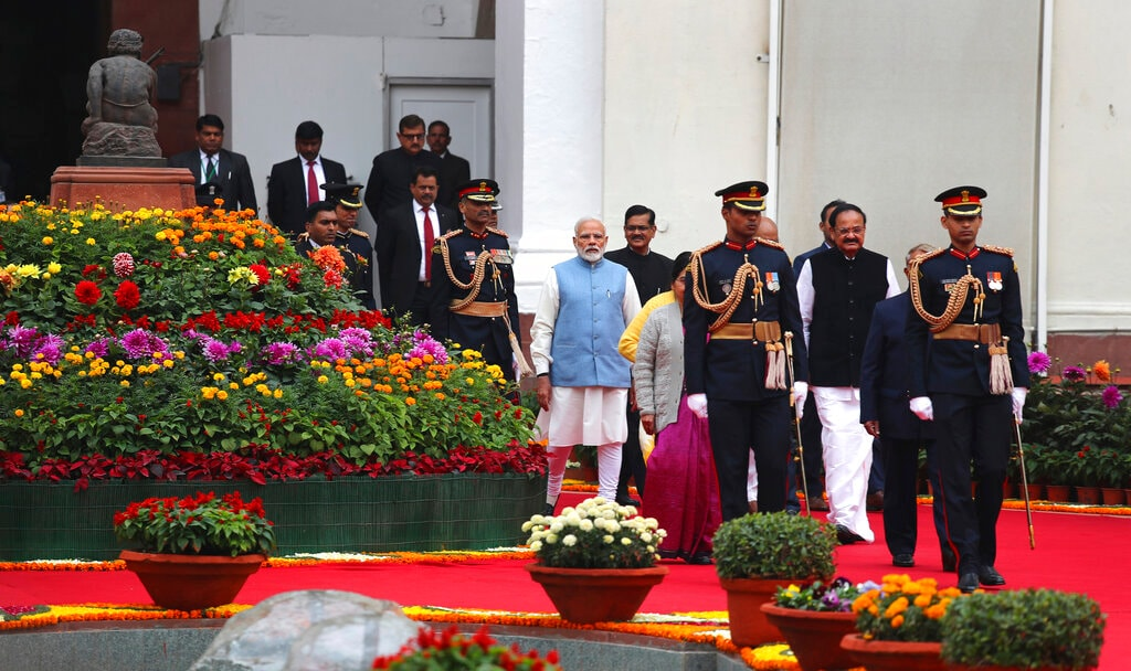 Prime Minister Narendra Modi, center left in blue vest, Vice President Venkaiah Naidu, second right, along with other dignitaries enter the central hall of the Parliament in a procession to mark the beginning of the budget session in New Delhi, India, Thursday, January 31, 2019. (AP Photo/Manish Swarup)