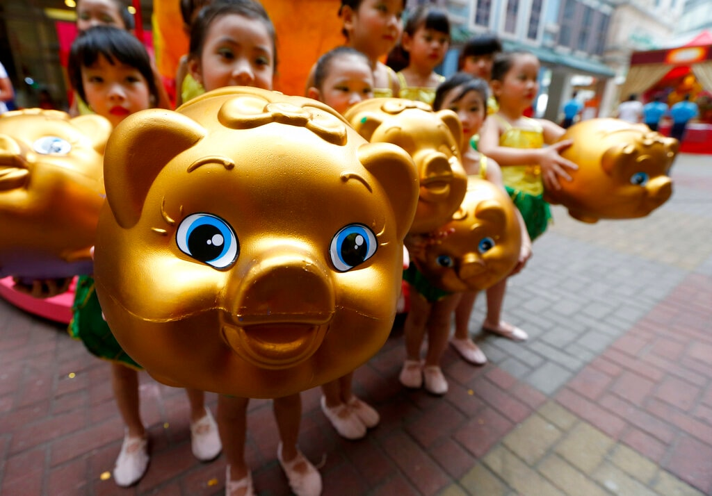 In this Friday, February 1, 2019, photo, Filipino-Chinese display piggy banks at the start of celebrations leading to next week's Lunar New Year in Chinatown, Manila, Philippines. (AP Photo/Bullit Marquez)