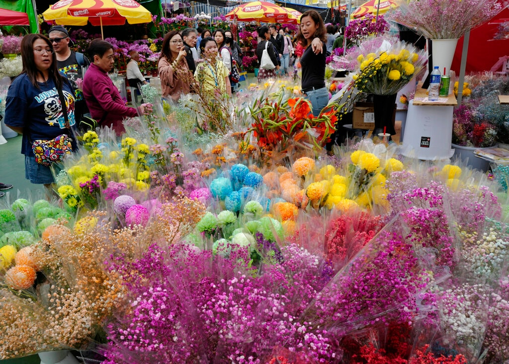 In this Monday, February 4, 2019, photo, people buy flowers at a New Year market in Hong Kong's Victoria Park. (AP Photo/Vincent Yu)