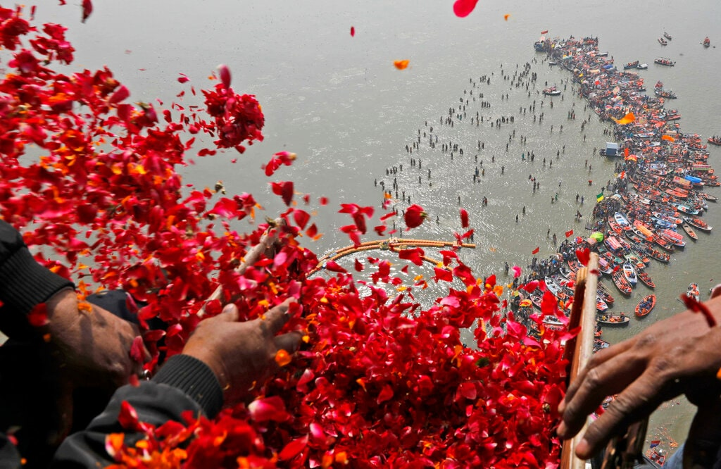 Government officials throw flowers from a helicopter on to thousands of Hindu devotees taking dips at Sangam, the confluence of three sacred rivers the Yamuna, the Ganges and the mythical Saraswati, on Mauni Amavsya or the new moon day, the most auspicious day during the Kumbh Mela or the Pitcher Festival, in Prayagraj, Uttar Pradesh state, India, Monday, Feb. 4, 2019. (AP Photo/Rajesh Kumar Singh)