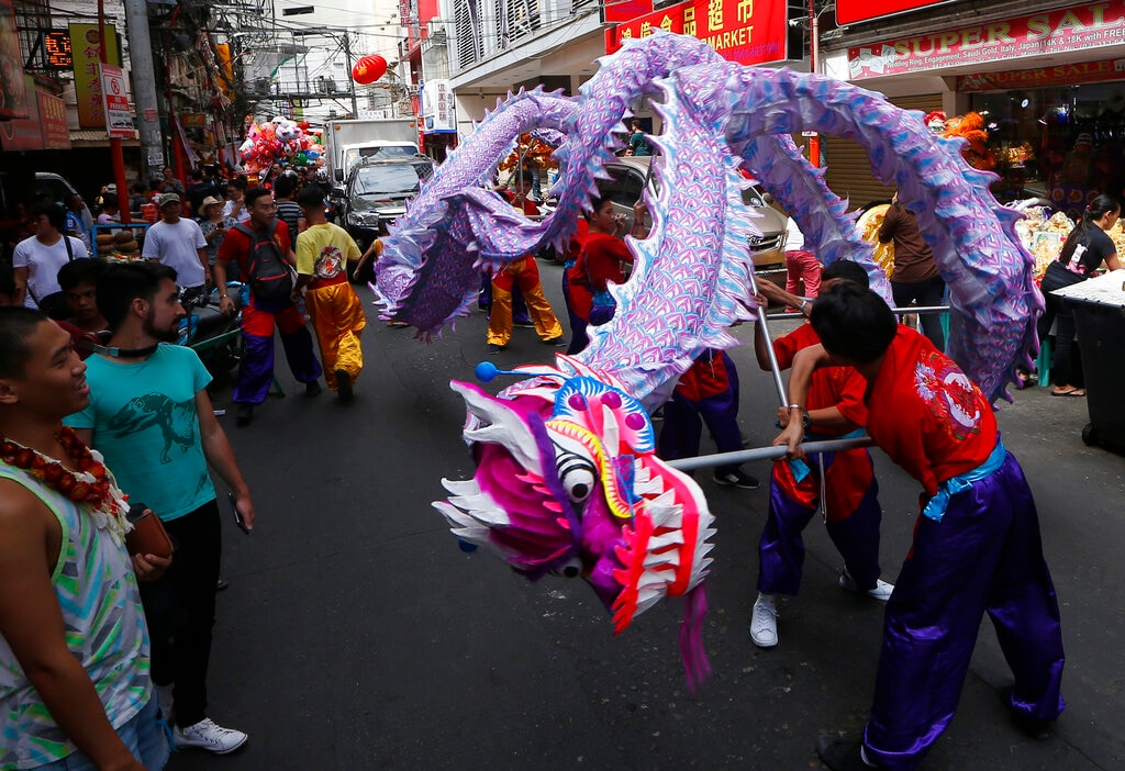 In this Monday, February 4, 2019, photo, Filipino-Chinese perform a dragon dance on Chinese New Year's Eve at Manila's Chinatown district in Manila, Philippines. This year is the Year of the Earth Pig in the Chinese Lunar calendar and is supposed to represent abundance, diligence and generosity. (AP Photo/Bullit Marquez)