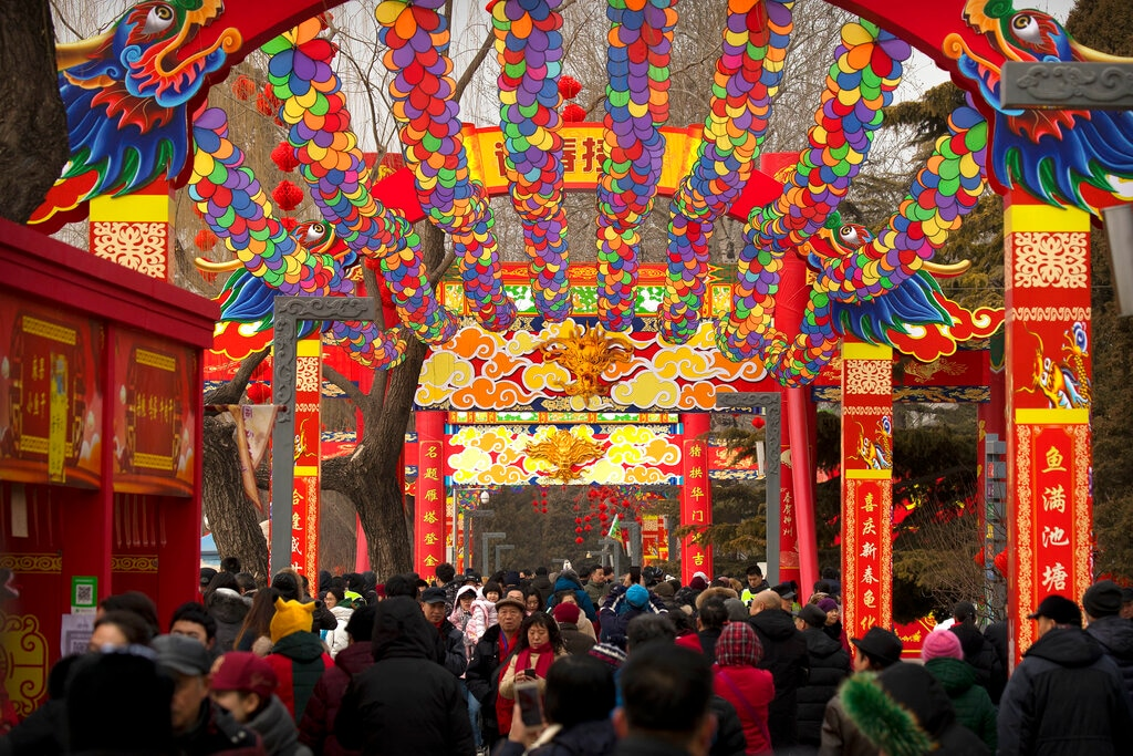People walk under a canopy decorated with spinning colored fans at a temple fair at Longtan Park in Beijing, Wednesday, February 6, 2019. Chinese people are celebrating the second day of the Lunar New Year on Tuesday, the Year of the Pig on the Chinese zodiac. (AP Photo/Mark Schiefelbein)