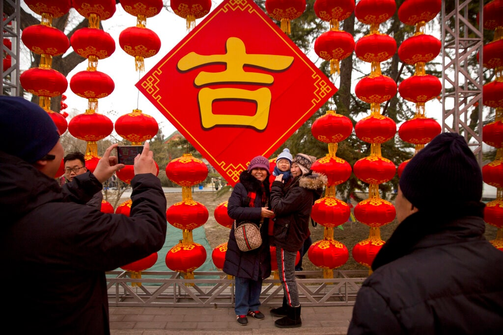 People pose for photos in front of a wall of lanterns at a temple fair at Longtan Park in Beijing, Wednesday, February 6, 2019. Chinese people are celebrating the second day of the Lunar New Year on Tuesday, the Year of the Pig on the Chinese zodiac. (AP Photo/Mark Schiefelbein)