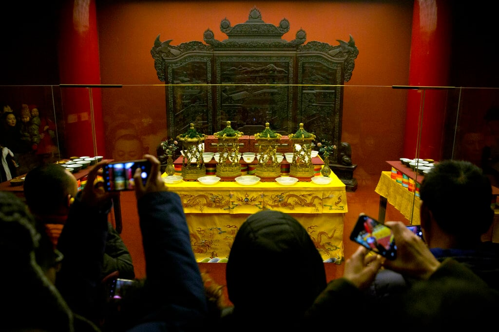 Tourists take photos of an exhibition about traditional imperial celebrations of the Lunar New Year at the Forbidden City in Beijing, Friday, February 8, 2019. Chinese people are celebrating a week-long holiday for the Lunar New Year, the Year of the Pig on the Chinese zodiac. (AP Photo/Mark Schiefelbein)