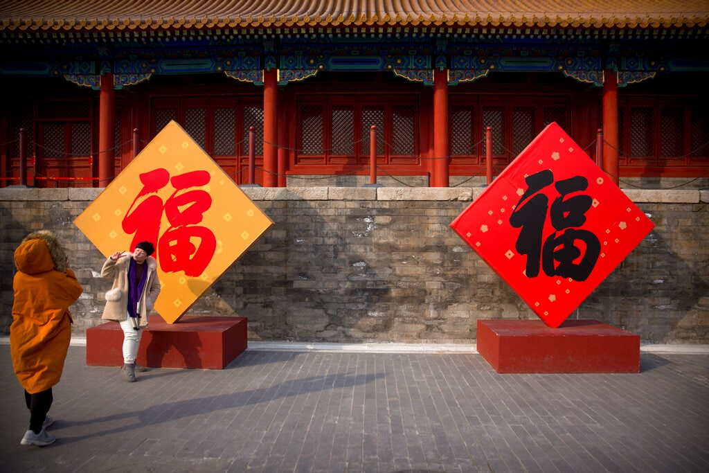 A woman poses for photos with the Chinese character for