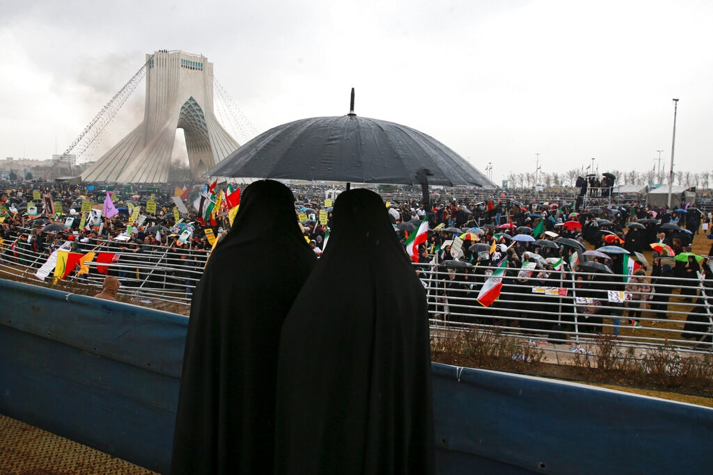 Two women shelter from the rain during a ceremony celebrating the 40th anniversary of the Islamic Revolution, at the Azadi, Freedom, Square in Tehran, Iran, Monday, February 11, 2019. In Tehran, crowds streamed in the rain from a dozen of the capital's far-flung neighbourhoods to mass in central Tehran Azadi, or Freedom Square, waving Iranian flags and chanting