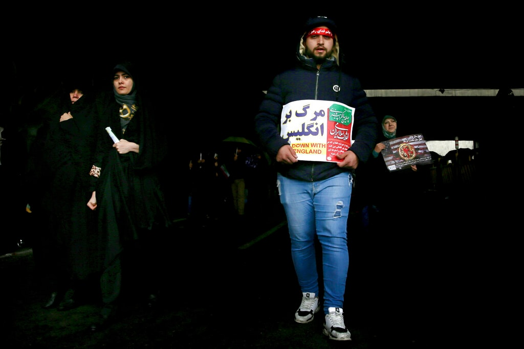 A man holds a placard that reads in Farsi,